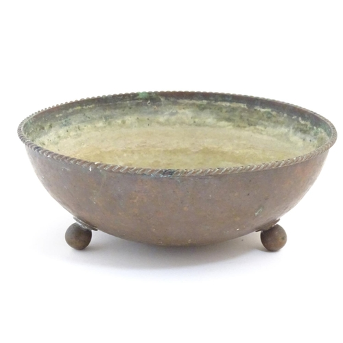 968 - An Arts & Crafts Dryad Lester copper bowl with three brass ball feet and a twist rim. Impressed make...