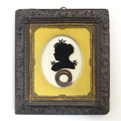 970 - A 19thC oval reverse glass silhouette portrait miniature depicting a woman with a bow in her hair an...