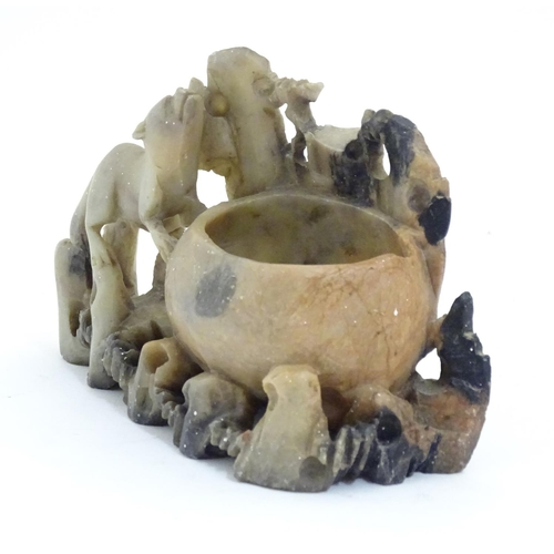 1037 - Three Oriental carved soapstone brush washer pots, decorated with carved animals and foliage. The la...