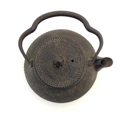 1040 - A Japanese cast iron teapot with a swing handle. Character marks below spout. Approx. 2 3/4