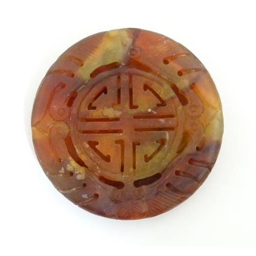 1045 - An Oriental hardstone roundel carving depicting stylised a dragon and scrolling foliage. Approx. 2 1...