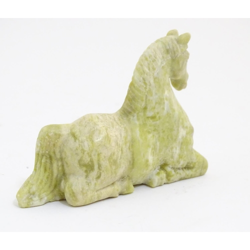 1053 - An Oriental jade/ hardstone model of a horse, together with two soapstone examples. Largest approx. ...