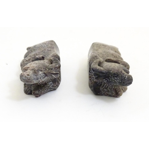 1054 - A pair of Oriental carved soapstone models of recumbent water buffalo. Incised marks under. Approx. ...