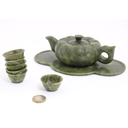 1065 - An Oriental carved soapstone small tea set with a lobed teapot, six tea bowls, and a quatreform tray...