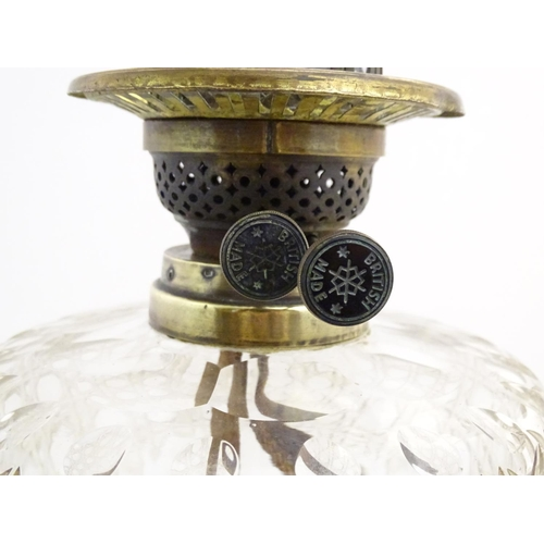 908 - A late 19thC / early 20thC brass oil lamp with cut glass reservoir. The whole standing approx. 35