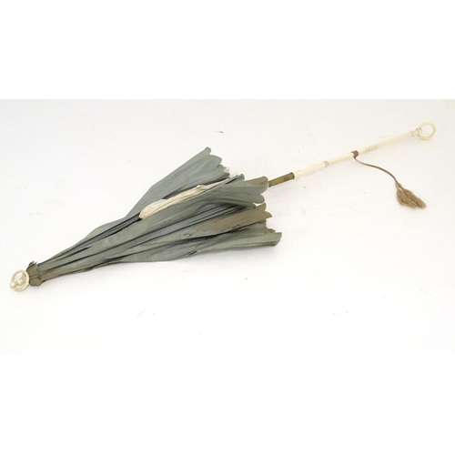 942 - A 19thC folding parasol with a carved ivory handle. Approx. 27 1/4