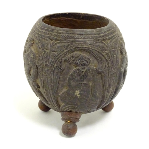 950 - An Indian carved coconut bowl with relief figural / deity decoration. Together with two carved spoon...