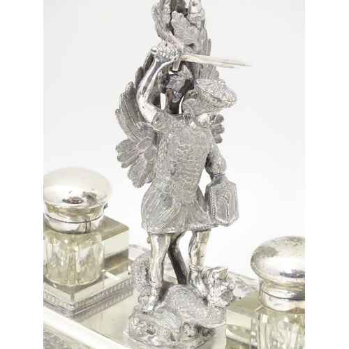 482 - A silver plate standish with central epergne flute supported by cast figure of St George slaying the...