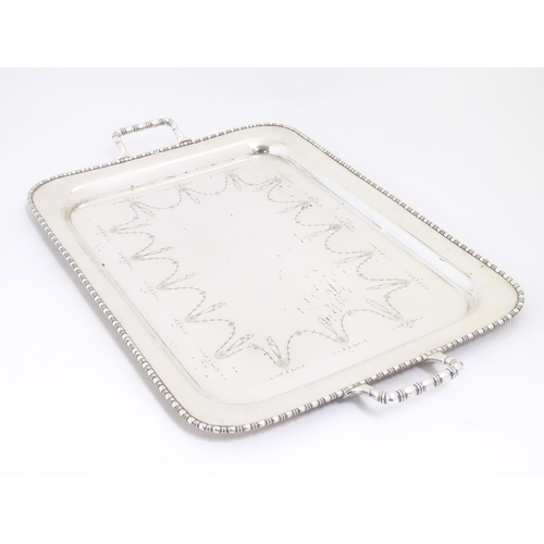 498 - A large silver plate two handled tray with engraved decoration 26