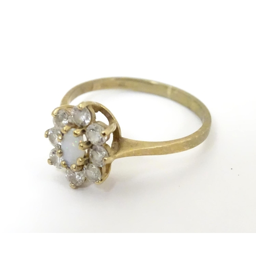 507 - A 9ct gold ring set with opal like cabochon bordered by white stones. Ring size approx L