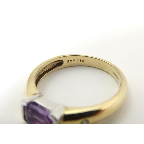 511 - A 9ct gold amethyst and diamond ring, the central amethyst flanked by two diamonds  . Ring size appr...