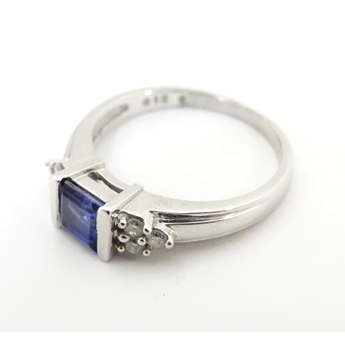 513 - A 9ct white gold ring set with central sapphire flanked by diamonds. Ring size approx L 1/2