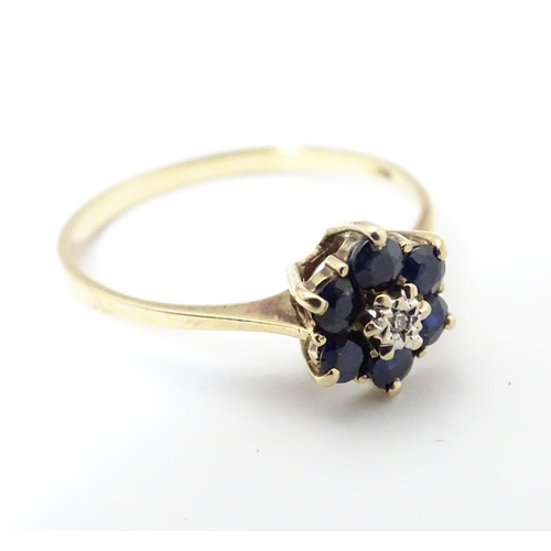 515 - A 9ct gold ring set with central diamond bordered by 6 sapphires in a cluster setting. Ring size app...