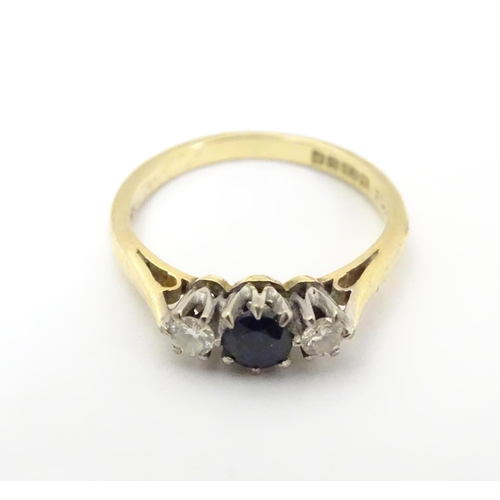 519 - An 18ct  ring set with dark blue spinel flanked by diamonds. Ring size approx I...