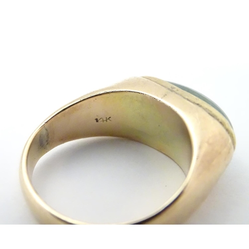530 - A 14ct gold ring set with jade cabochon. Ring size approx. P 1/2