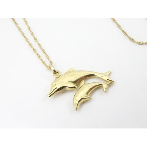 545 - A 9ct double dolphin pendant on a gold chain 16