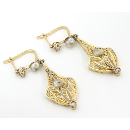 556 - A pair of gold drop earrings set with diamonds and pearls. Approx 1 1/2