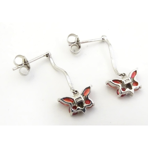 583 - 9ct white gold drop earrings with butterfly detail red stones. 3/4