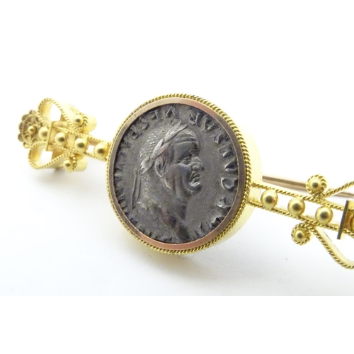 593 - A Victorian gold and gilt metal bar brooch with filigree style decoration set with coin like decorat...
