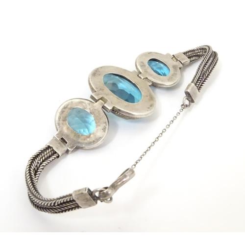 598 - A white metal bracelet set with three large graduated aquamarine coloured stones.