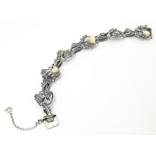 622 - A German .800 silver bracelet with oak leaf and acorn detail set with deer's tooth detail.