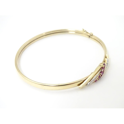624 - A 9ct gold bracelet of bangle form set with rubies and diamonds