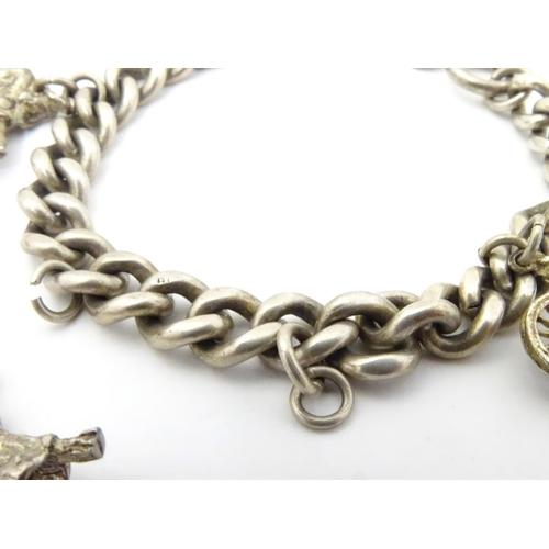 633 - A silver charm bracelet set with white metal charms