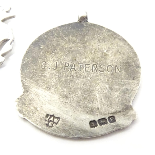 647 - A hallmarked silver fob medal, the obverse decorated with the insignia of the National Safety First ...