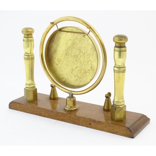1131 - A 20thC brass table dinner gong and beater mounted on a rectangular oak base. Approx. 10