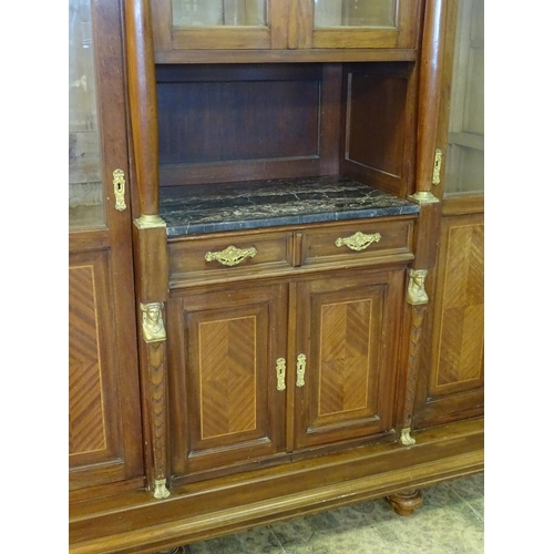 1384 - A large continental mahogany cabinet with a moulded cornice above gilt metal mounts and glazed doors...