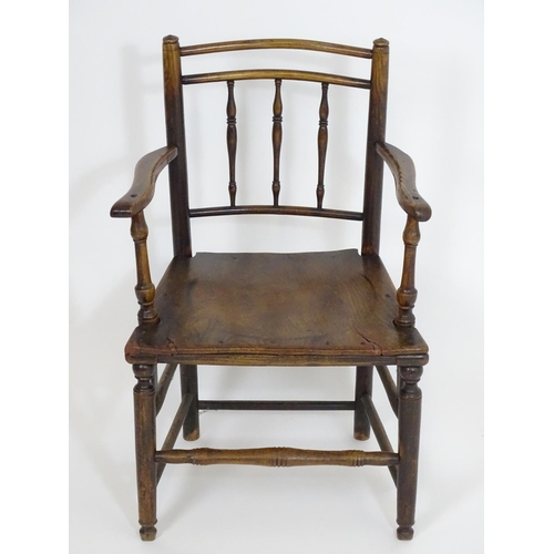 1401 - An early 19thC spindle back open armchair, with bowed top rails, swept arms and turned uprights abov...