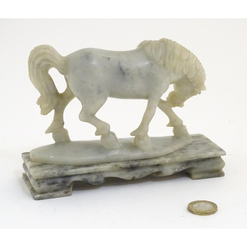 998 - An Oriental soapstone carving modelled as a horse on a rectangular base. Approx. 5