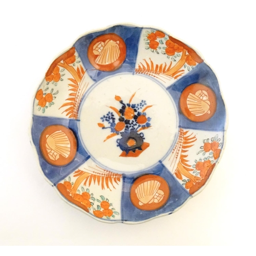 8 - Two Japanese plates in the Imari palette with scalloped edges, the centre decorated with flowers in ...