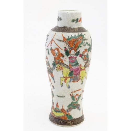 9 - A Japanese crackle glaze vase decorated in famille verte with warriors and horses. Character marks t...