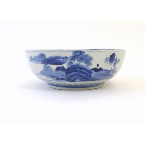 15 - A Chinese blue and white bowl with hand painted decoration depicting an Oriental landscape with pago...