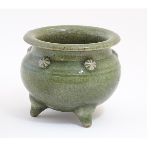 25 - A Chinese three footed censor with a crackle glaze and floral roundels in relief. Approx. 3 1/4