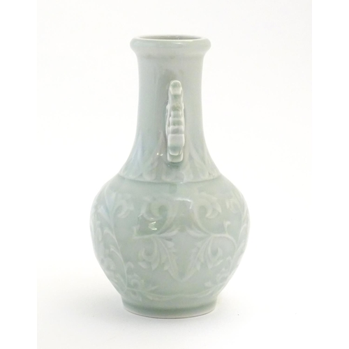 30 - A Chinese celadon green baluster vase with twin handles and stylised foliate design. Approx. 6 1/4