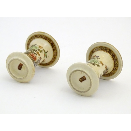 46 - A pair of Japanese miniature Satsuma vases with flared rims and bases, decorated with flowers and fo...