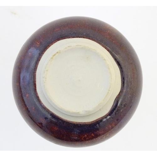 17 - A bottle vase with a mottled sang de boeuf style glaze. Approx. 6 3/4