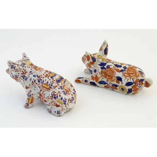 29 - Two Oriental models of pigs decorated in the Imari palette with floral and foliate detail. Character...