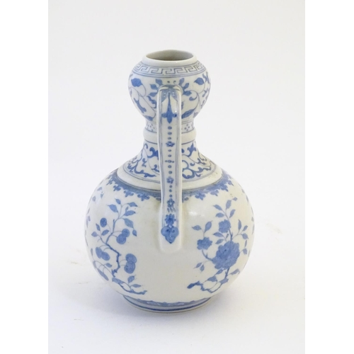3 - An Oriental blue and white double gourd vase with twin handles decorated with scrolling floral and f...