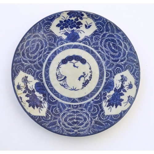 44 - An Oriental blue and white plate with stylised peony detail, and stylised scrolling flower motifs to...