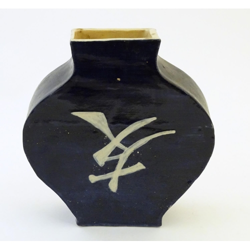 47 - An Oriental slab vase with stylised character mark detail, possibly Japanese. Approx. 10 1/4