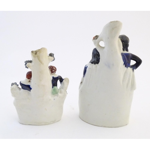 59 - Five assorted Staffordshire pottery figures comprising two models of shepherds and their sheep, two ...