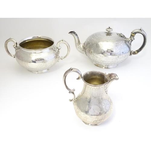 326 - A Victorian three piece silver tea set, comprising a teapot, milk jug, and twin handled sugar bowl. ...