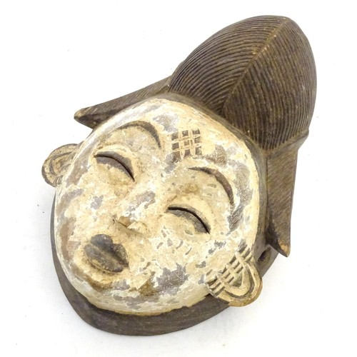 """Ethnographic / Native / Tribal: A carved African mask with white painted detail. Approx. 12"""" high"""