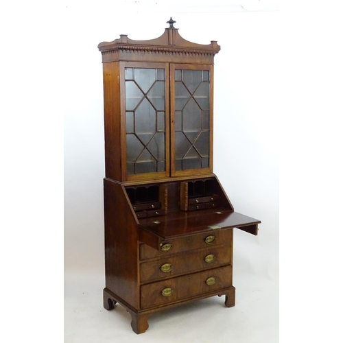 1403 - A late 18thC mahogany Georgian bureau bookcase with a carved pediment and moulded frieze above two a...