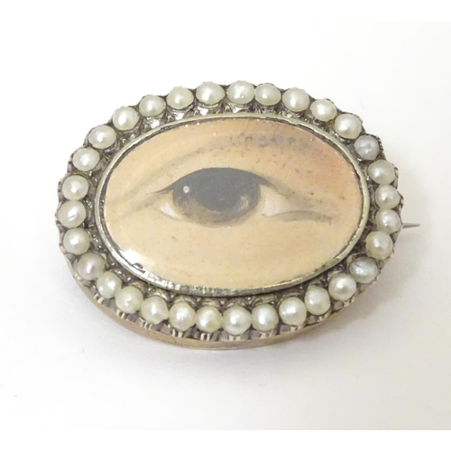 """A Georgian Lovers eye brooch, the oval brooch set with hand painted miniature depicting of a brown eye within a seed pearl border Approx 1"""" wide"""