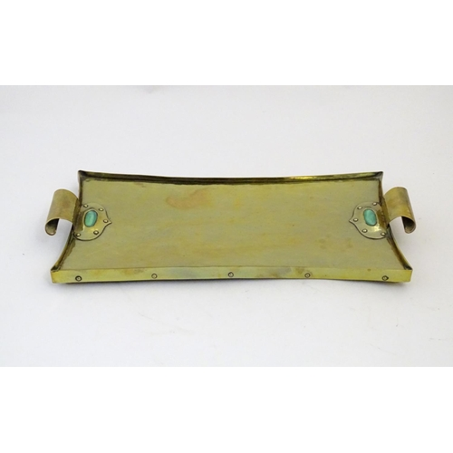 1010 - An Arts & Crafts brass tray with twin scroll handles and Ruskin style cabochon and rivet detail. App...
