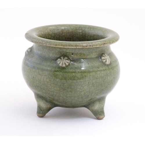 15 - A Chinese three footed censor with a crackle glaze and floral roundels in relief. Approx. 3 1/4